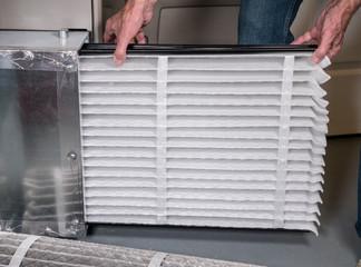 Senior man inserting a new air filter in a HVAC Furnace