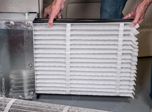 Canvas-taulu Senior man inserting a new air filter in a HVAC Furnace