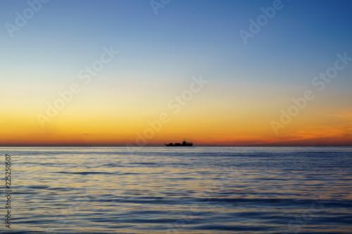Fotografia, Obraz  Silhouette of sailing ship far away at the sea horizon during sunset