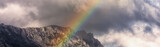 Fototapeta Tęcza - rainbow in the mountains on a cloudy day panoramic landscape