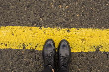 Women's Boots On The Yellow Border Line That Attract The Attention