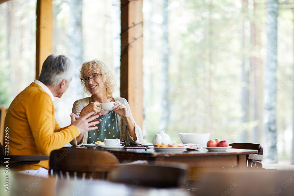 Fototapeta Positive beautiful mature couple in casual clothing sitting at table and drinking coffee at veranda while chatting in tranquil place