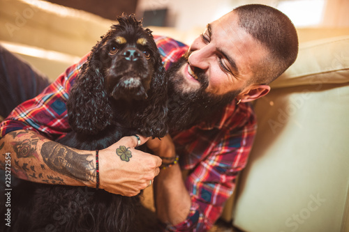 Handsome man with cute dog at home Canvas Print
