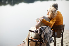 Rear View Of Dreamy Fashionable Senior Couple Sitting On Chairs And Relaxing With Coffee Cup On Pier, Elderly Man Embracing Beloved Woman At Romantic Date
