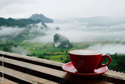 Photo Hot coffee latte cappuccino in red cup on wooden terrace with beautiful scenic view nature background of misty morning mountain in Phayao, Thailand
