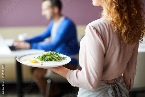 Obraz Close up of waitress in pink blouse carrying fried eggs with greens to restaurant visitor during breakfast time - fototapety do salonu