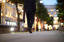 Businessman With Briefcase Walking Down Street In The Evening Along Green Trees