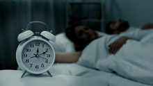 Young Couple Lying Asleep In Bed At Night With Clock Standing Near, Sleep Phases