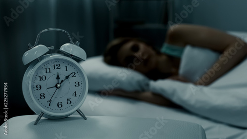 Fotografía  Young lady resting in her bed, midnight time shown on alarm clock, night dreams