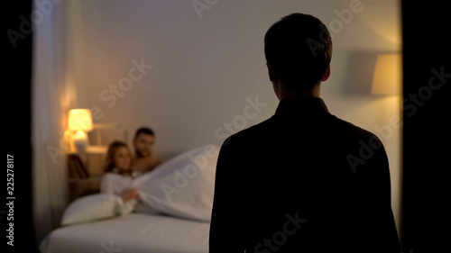 Foto Man looking at his wife with lover in bed, unfair relations, partner cheating