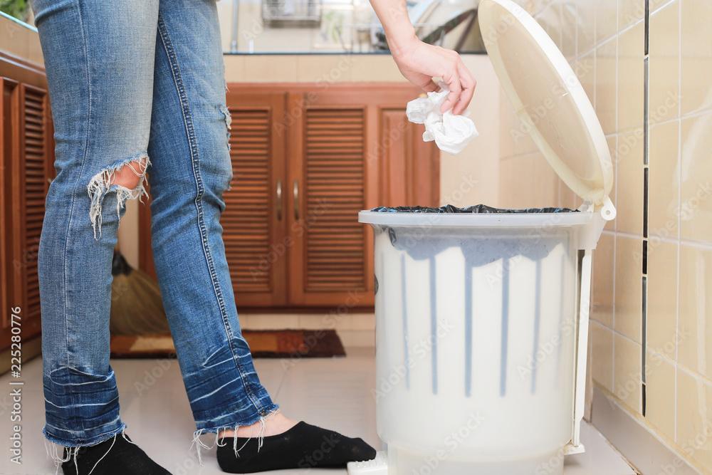 Fototapeta Woman putting empty plastic bag in recycling bin in the kitchen.