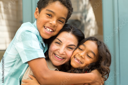 Photo Happy Hispnaic mother laughing and talking with her children.