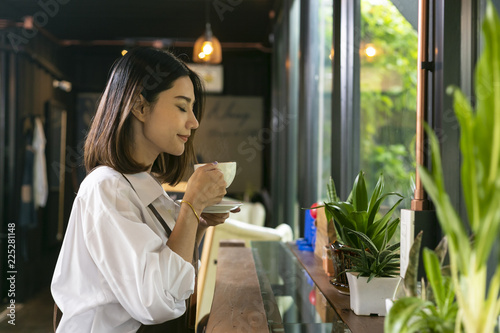 Fotografia  Asian woman smelling and drinking hot coffee with feeling good in cafe
