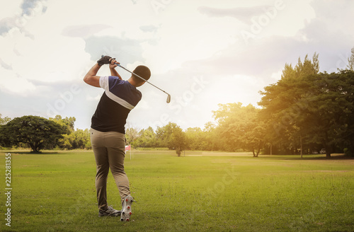 Poster Golf Golfer hitting golf shot with club on course at evening time.