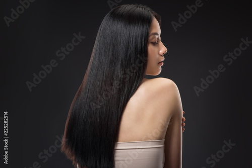 Fotografie, Obraz back view of beautiful asian woman with straight and shiny hair isolated on blac