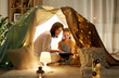 canvas print picture - family, hygge and technology concept - happy mother and little daughter with tablet pc computer in kids tent at night at home