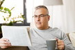 leisure, information, people and mass media concept - man reading newspaper and drinking coffee at home