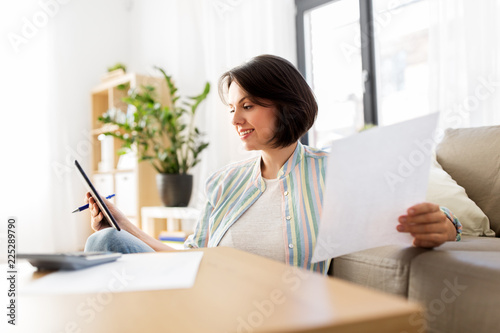 Fotografia, Obraz  business, savings, finances and people concept - woman with tablet pc, papers an