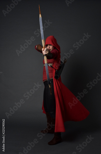 Photographie full length portrait of brunette girl wearing red medieval costume and cloak, holding a bow and arrow