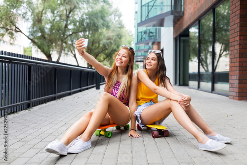 Staande foto Hoogte schaal friendship, leisure and technology concept - happy teenage girls or friends with skateboards on city street taking selfie by smartphone in summer