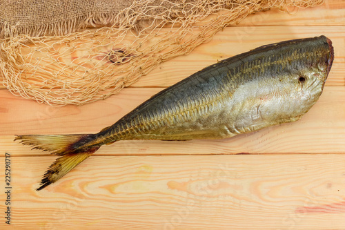 Smoked Atlantic horse mackerel without head on a wooden surface