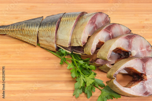 Valokuva  Sliced smoked Atlantic horse mackerel on cutting board close-up