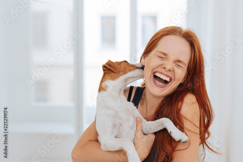 Fotografia Laughing young woman being licked by a dog