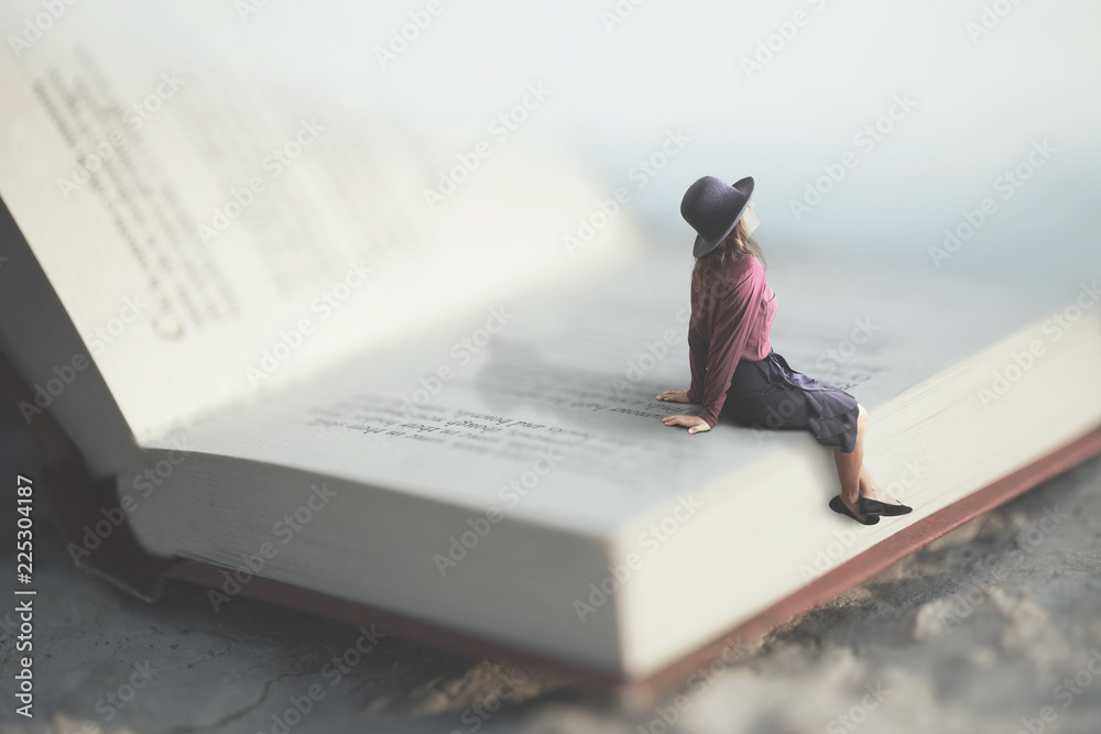 Fototapeta surreal moment of a woman relaxes sitting on a giant book