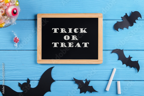 Wall Murals Newspapers Trick or treat text written on blackboard with decorative paper bats, eyeball shaped candy, gummy worms, spiders & bones. Halloween decor concept. Background, copy space, close up, top view, flat lay.