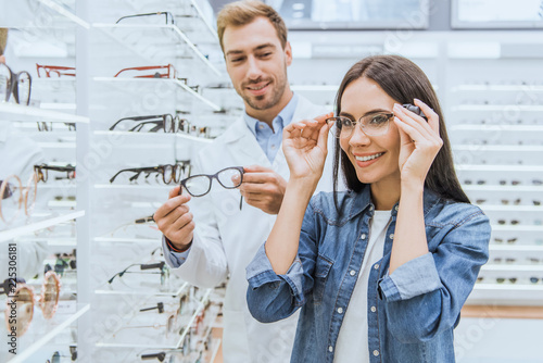 Fotomural happy woman choosing eyeglasses while male oculist standing near with another ey