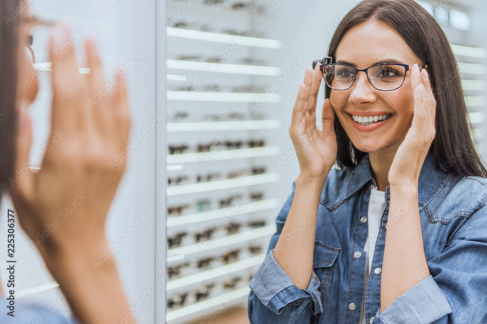 Fototapeta partial view of smiling woman choosing eyeglasses and looking at mirror in optica