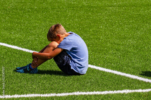 Vászonkép Sad disappointed boy sitting on the grass in stadium