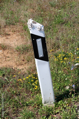 Fotografía  Leaning black and white plastic roadside pole with reflective patch covered on t