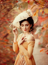 A Young Brunette Woman With An Elegant, Hairstyle In A Hat With A Strass Feathers. Lady In A Yellow Vintage Dress Walks Through The Autumn Landscape. Artistic Portrait