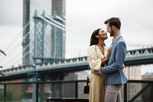 Love Story In New York. Gorgeous Couple Of American Man With Beard And Tender Eastern Woman Hug Each Other Before The Cityscape Of Brooklyn Bridge Somewhere In New York