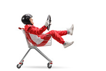 Elderly Man In A Racing Suit With Helmet Holding A Steering Wheel And Sitting Inside A Shopping Cart