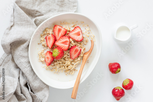 Oatmeal porridge with strawberries on white background. Healthy breakfast concept, healthy eating, lifestyle