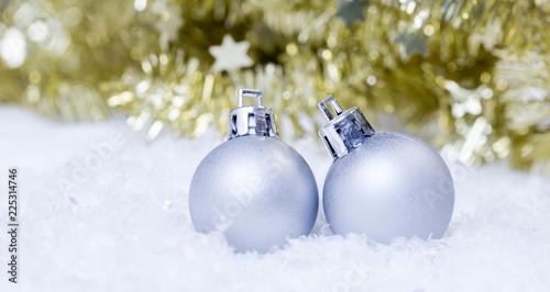 två silver julgranskulor på snö med guld glitter i bakgrunden