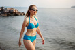 Young pretty woman in a blue swimsuit is walking along a sandy beach by the sea.