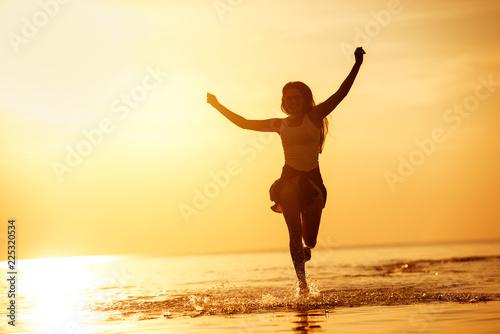 Stampa su Tela  Happy girl run in sunset lake