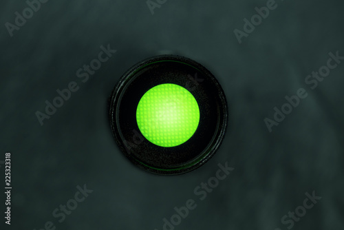 Fotografía  An overhead photo of a vibrant green button on a dark panel with copy space