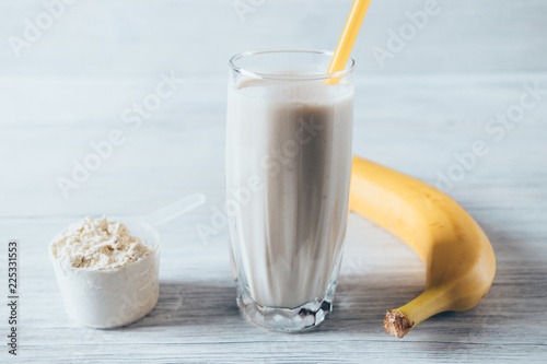 Fotografie, Obraz  Glass of sports shake next to ripe banana and dry powder