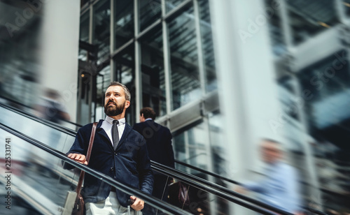 Photo Hipster businessman using escalator in city, travelling to work.