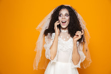 Image Of Dead Bride Zombie On Halloween Wearing Wedding Dress And Scary Makeup Talking On Cell Phone, Isolated Over Yellow Background