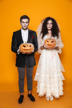 Creepy Halloween Bride And Groom Looking Camera And Holding Pumpkin