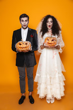Surprised Halloween Bride And Groom Looking Camera And Holding Pumpkin
