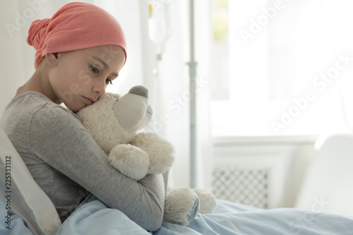 Weak girl with cancer wearing pink headscarf and hugging teddy bear Canvas Print