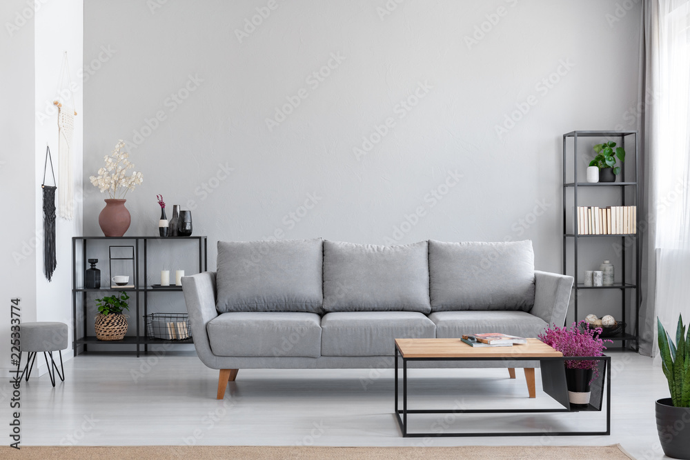 Fototapeta Flowers in wooden table in front of grey settee in modern simple apartment interior with stool. Real photo