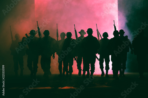 Photo  soldiers walkers carrying a gun in the holding hand and smoke with lighting back