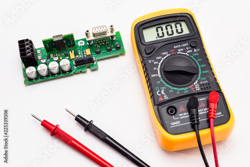 Fotografie, Obraz  Electric multimeter with red and black probe, display indicating zero, with printed circuit board